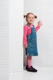 Śmieszna mała dziewczynka pozuje w białej scenerii w modnym odziewa Obrazy Stock