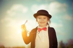 Śmieszna mała dziewczynka w łęku krawacie i dęciaka kapeluszu Zdjęcie Stock