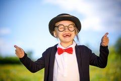 Śmieszna mała dziewczynka w łęku krawacie i dęciaka kapeluszu pokazuje aprobaty Obraz Royalty Free