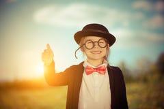Śmieszna mała dziewczynka w łęku krawacie i dęciaka kapeluszu pokazuje kciuk up Fotografia Royalty Free