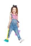 Śmieszna mała dziewczynka w drelichowy kombinezonów zamiatać obrazy royalty free