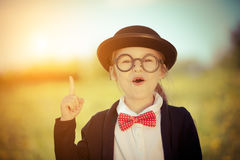 Śmieszna mała dziewczynka w szkłach, łęku krawacie i dęciaka kapeluszu, Obrazy Stock