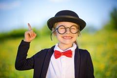 Śmieszna mała dziewczynka w szkłach, łęku krawacie i dęciaka kapeluszu, Fotografia Royalty Free