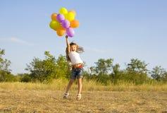 Śmieszna mała dziewczynka z balonami, odbija się Obraz Royalty Free