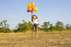 Śmieszna mała dziewczynka z balonami, odbija się Obrazy Royalty Free