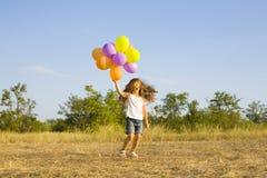 Śmieszna mała dziewczynka z balonami, odbija się Zdjęcie Royalty Free