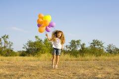 Śmieszna mała dziewczynka z balonami, odbija się Zdjęcia Royalty Free