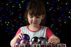 Śmieszna mała dziewczynka z pudełkiem boże narodzenie piłki Zdjęcie Stock