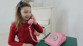 Śmieszna mała dziewczynka z różowym retro telefonem w domu Trzyma w ręk menchii retro telefonie i opowiada z matką zdjęcie wideo