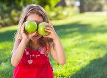 Śmieszna mała dziewczynka z zielonymi jabłkami Zdjęcia Royalty Free