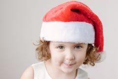 Śmieszna mała kędzierzawa blondynki dziewczyna w Santa kapeluszu obraz royalty free