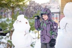 Śmieszna małe dziecko chłopiec robi bałwanu i je marchewki, bawić się mieć zabawę z śniegiem, outdoors na zimnym dniu Aktywny cza Obrazy Royalty Free