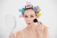 Śmieszna naturalna brown z włosami kobieta w włosianych curlers stosuje proszek na jej twarzy Fotografia Stock