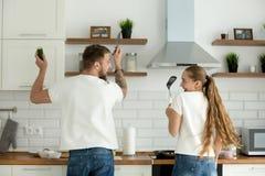 Śmieszna para ma zabawy kucharstwo w kuchni wpólnie, tylni widok fotografia stock