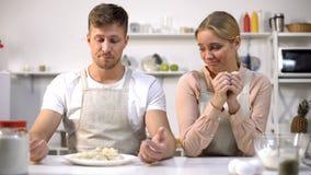 Śmieszna para patrzeje surowego ciasto, złe kuchenki, kulinarni kursy dla amatorów obrazy royalty free