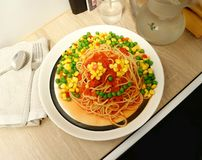 Śmieszna patrzeje «karmowa twarz robić spaghetti, pomidorowy kumberland i mieszanka warzywa, fotografia stock
