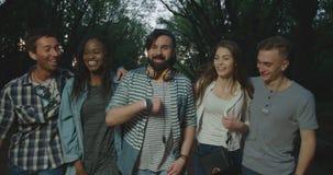Śmieszna rozmowa szczęśliwi modnisiów przyjaciele chodzi w wieczór parku zbiory