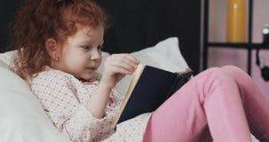 Śmieszna rudzielec mała dziewczynka czyta książkę na łóżku w jej sypialni zbiory