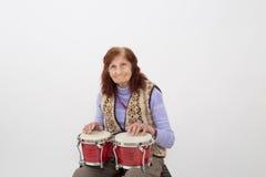 Śmieszna starsza dama bawić się bongo Zdjęcie Stock
