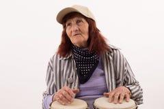 Śmieszna starsza dama bawić się bongo Obraz Stock