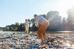 Śmieszna starsza para bawić się z wodą przy rzeką w słonecznym dniu obraz royalty free