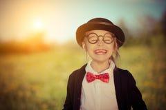 Śmieszna szczęśliwa mała dziewczynka w łęku krawacie i dęciaka kapeluszu Zdjęcie Stock