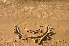 Śmieszna twarz rysująca na mokrym piasku blisko morza fotografia royalty free
