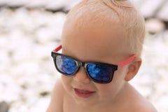 Śmieszna uśmiechnięta chłopiec w okularach przeciwsłonecznych na plaży Kamienie odbijają w szkłach Mały szef na wakacje Zdjęcia Stock
