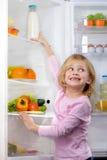 Śmieszna uśmiechnięta dziewczyna próbuje podnosić jedzenie od fridge Fotografia Royalty Free