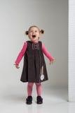 Śmieszna uśmiechnięta mała dziewczynka pozuje w białej scenerii w modnym odziewa Zdjęcia Stock