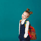 Śmieszna uśmiechnięta mała dziewczynka skacze f i ma z dużym plecakiem zdjęcia royalty free
