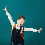 Śmieszna uśmiechnięta mała dziewczynka skacze f i ma z dużym plecakiem obraz royalty free
