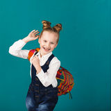 Śmieszna uśmiechnięta mała dziewczynka skacze f i ma z dużym plecakiem zdjęcie stock