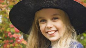 Śmieszna uśmiechnięta mała dziewczynka w czarownica kapeluszu pozuje przy kamerą, Halloween partyjny strój zbiory