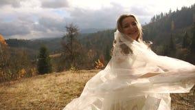 Śmieszna uśmiechnięta panna młoda szczęśliwie bawić się z jej przesłoną w pogodnych złotych górach i zbiory