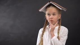 Śmieszna uczennica z książką na kierowniczym planistycznym praca domowa rozkładzie, edukacji pojęcie zbiory wideo