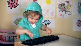 Śmieszna urocza dziecko dziewczyna pisać na maszynie komputerową klawiaturę i patrzeje kamerę i uśmiech zdjęcie wideo