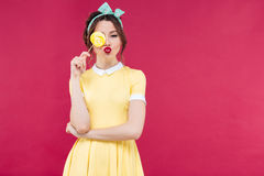 Śmieszna urocza pinup dziewczyna zakrywał jeden oko z żółtym lizakiem Obrazy Royalty Free