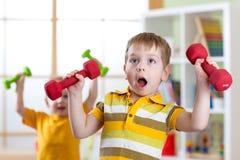 Śmieszne dzieciak chłopiec ćwiczy z dumbbells w domu Zdrowy życie, sportive dzieci Zdjęcie Royalty Free