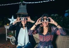 Śmieszne kobiety trzyma smartphones pokazuje samiec oczy zdjęcia stock