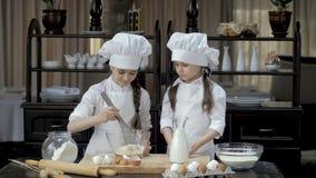 Śmieszne młode dziewczyny przygotowywają ciasto w kuchni zbiory wideo