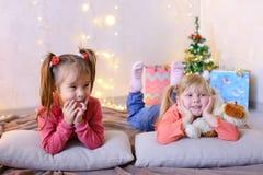 Śmieszne małe dziewczynki śmiają się i opowiadają, pozujący kłamać na podłoga i dalej fotografia royalty free