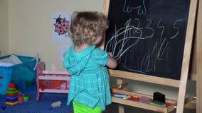 Śmiesznego małego dziecka blondynki berbecia dziewczyny śliczny rysunek z kredą na czerni desce zdjęcie wideo