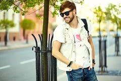 Śmiesznego uśmiechniętego modnisia przystojny mężczyzna w modnisia płótnie w ulicie zdjęcia stock