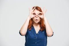 Śmiesznej ślicznej młodej kobiety throug przyglądający szkła robić palce zdjęcia stock