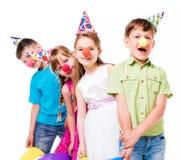 Śmieszni dzieci z błazenów nosami i urodzinowymi kapeluszami fotografia stock