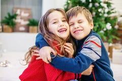 Śmieszni dzieciaki ściskają Chłopiec i dziewczyna Szczęśliwi boże narodzenia Zdjęcie Stock