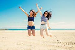 Śmieszni dziewczyn frinds skacze na plaży Fotografia Stock
