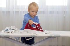 Śmieszny śliczny mały chłopiec gospodyni prasowanie odziewa Dzieciak angażujący w domowej pracie Fotografia Stock