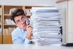 Śmieszny audytor sprawdza raporty z powiększać - szkło zdjęcia stock